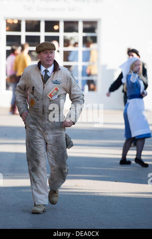 Chichester, West Sussex, UK. 14th Sep, 2013. Goodwood Revival. Goodwood Racing Circuit, West Sussex - Saturday 14th September. A man dressed in a period set of mechanics overalls walks past a lady in a vintage nurses uniform giving directions. Credit:  MeonStock/Alamy Live News - Stock Image