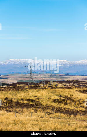 Electricity pylons on the eastern edge of the Lake District National Park, near Shap, Cumbria. Part of the national grid, carrying powerlines towards  - Stock Image