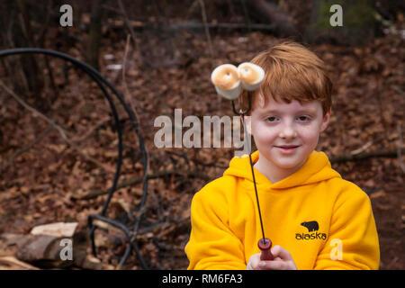 Young boy outside toasting marshmallows, USA - Stock Image