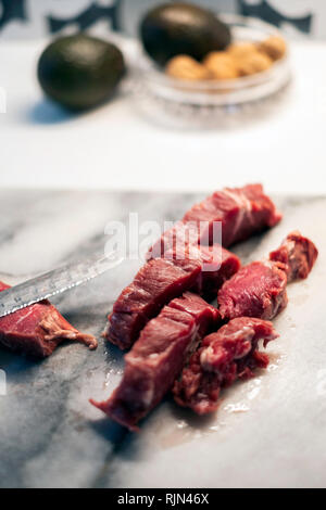 A marbled beef roast on a marble cutting board being cut up with a serrated knife. - Stock Image