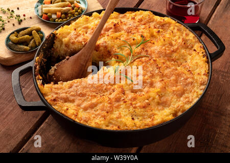 Homemade Shepherd's pie in a cooking pan with pickles and wine on a dark rustic wooden background - Stock Image