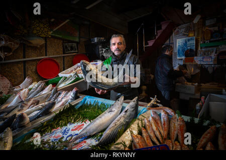 Fish monger selling large fish in the Grand Bazaar in Istanbul in Turkey. - Stock Image