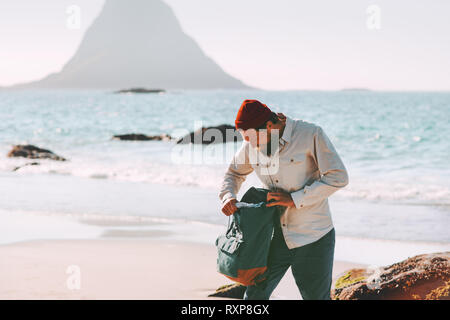 Man packing his backpack on sea beach traveling in Norway active lifestyle summer vacations outdoor adventure trip - Stock Image
