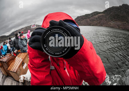 Person in red waterproof holding camera and taking photo of photographer - Stock Image