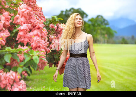 Happy lady stands near bush with pink flowers and enjoys - Stock Image