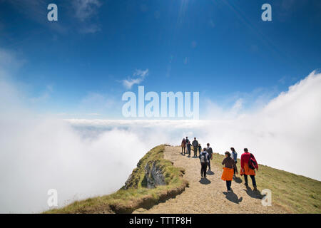 Hikers walking on cliff surrounded by clouds - Stock Image