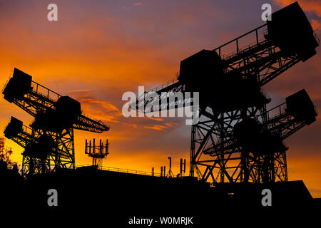 silhouette, of, ship, yard, cranes,silhouetted,against,sunset,sunrise,mobile phone,aerial,roof,top,mast,telephone,exchange,communications, - Stock Image