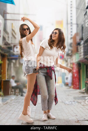 Young woman standing on a street listening to music - Stock Image
