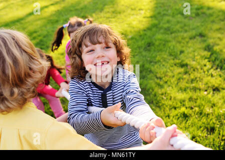 Children play tug of war in the park. - Stock Image