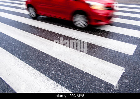 one red, fast, dangerous blurred car on the crosswalk, center top, no people, wet asphalt, empty space, - Stock Image