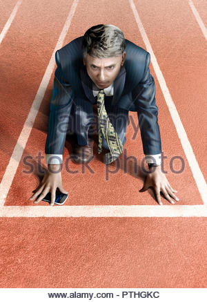 Businessman with money tie on starting line of athletics track - Stock Image