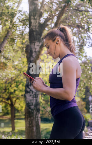 vertical photo of an attractive blonde sporty woman checking her phone app before running outdoors at park, fitness accessories - Stock Image