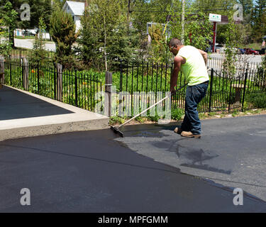 A worker spreading sealant on a driveway with a brush in Speculator, NY USA. - Stock Image