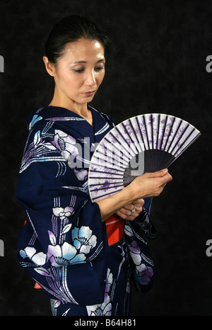 Japanese Woman in a Blue Kimono with a Fan - Stock Image