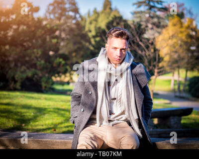 Handsome trendy young man, sitting in city park - Stock Image