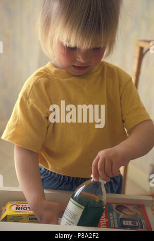 toddler pulling medicines out of drawer - Stock Image