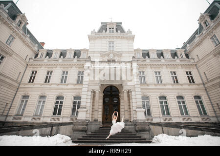 Beautiful ballerina jumping in white dress next to building on snow background. - Stock Image