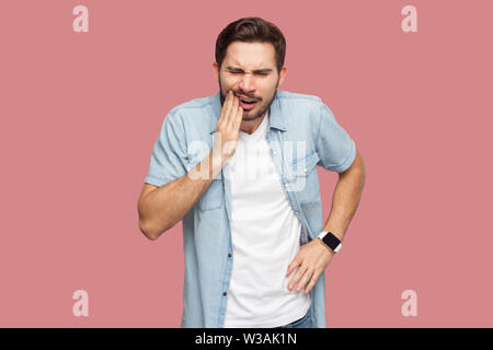 toothache or pain. Portrait of sad sick bearded young man in blue casual style shirt standing and touching his chik because feeling pain on tooth. ind - Stock Image