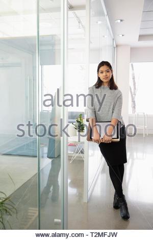 Portrait confident businesswoman in modern office - Stock Image