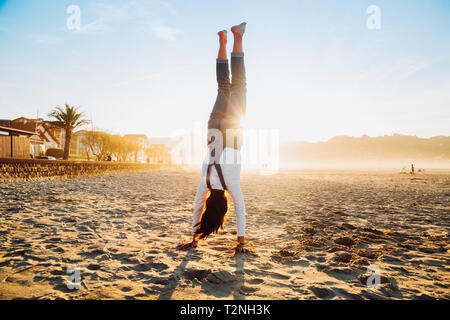 Little girl standing upside down on the beach at sunset - Stock Image