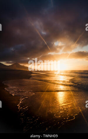 Dark beautiful nature outdoors sunset with sea waves and mountains in background - sunlight effect and wild natural beauty in outdoor scenic place for - Stock Image
