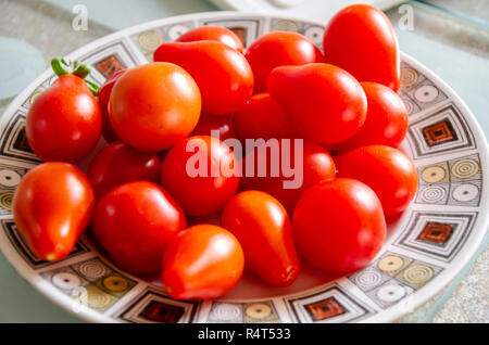 Red pear tomatoes on a plate. - Stock Image