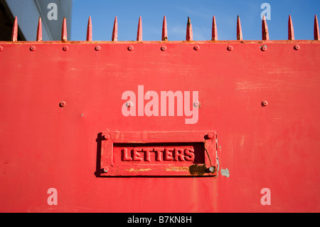 Old fashioned letter box in metal door with spikes - Stock Image