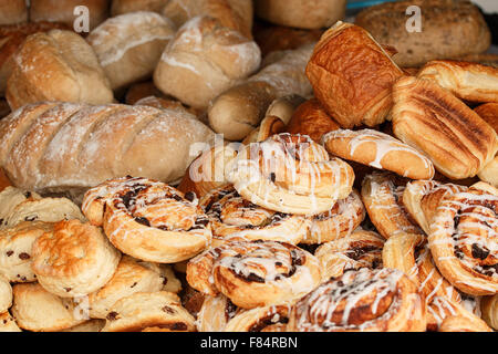 Selection of baked goods available from specialised bakers including buns; scones; pain au chocolate; pain; cobbs - Stock Image
