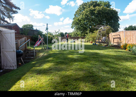 A view down a garden with a long, green lawn and a man with a lawnmower at the far end. A sunny day with blue sky and fluffy clouds. - Stock Image