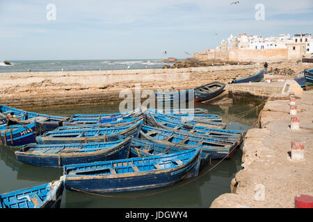 Blue painted boats belonging to fisherman lie inside the old harbour of Essaouira, Morocco - Stock Image