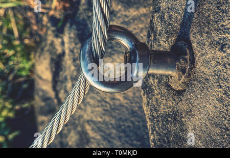 Stainless twisted rope anchored in rocky wall. Stair climbing and iron rope on mountain via ferrata - Stock Image