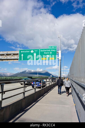 Ironworkers Memorial Bridge northbound in Vancouver, BC.  Highway heading towards Whistler with pedestrians walking across.  Winter 2019. - Stock Image