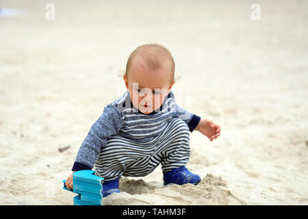 Cute Baby Boy Playing With Sand And Blue Plastic Shovel On The Beach - Stock Image