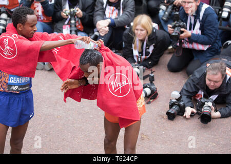 London, UK. 28th April 2019. Mosinet Geremew(Eth) 2nd, pours bottled water over Mule Wasihun(Eth) who finished 3rd in The 39th London Marathon at the Finish Line.Credit: Keith Larby/Alamy Live News - Stock Image