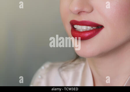 Work makeup artist. Female lips with red lipstick closeup. The girl smiles. - Stock Image