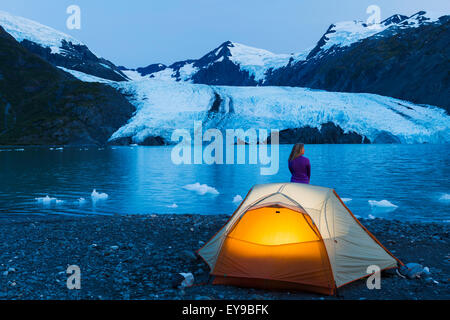 Female Camper Enjoying The View Of Portage Glacier At Dusk With A Lit Tent In The Foreground, Chugach National Forest, - Stock Image