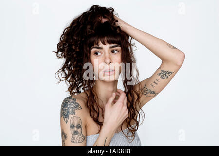 Portrait of tattooed young woman with hand in hair - Stock Image