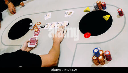 Close up of Texas Hold 'em Tournament game where two unidentifiable players are all in on classic coin flip situation of AK vs QQ - Stock Image
