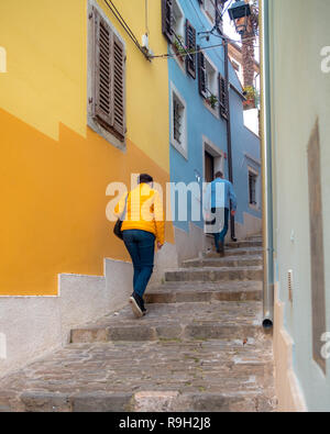Colorful street staircase of the Istrian town of Piran, with 2 walkers with jackets matching wall colors. - Stock Image