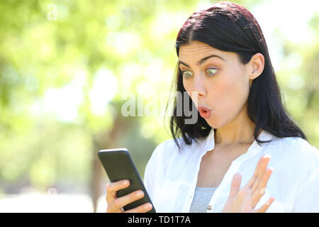 Surprised adult woman finds offers on smart phone standing in a park - Stock Image