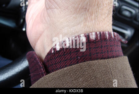 Driver hand with worn threads on shirt sleeve close up - Stock Image