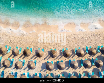 Greek beach with sunbeds and umbrellas top down aerial view - Stock Image