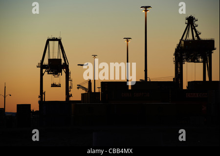 Silhouetted shipping terminal - Stock Image