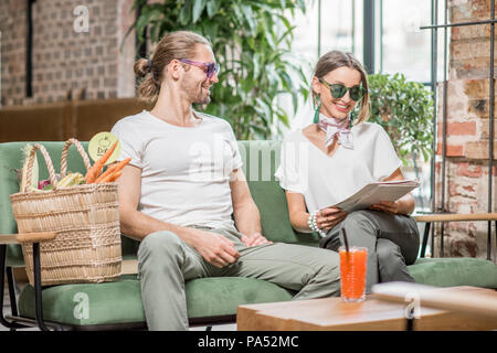 Young couple in white t-shirts sitting together on the green sofa with juice and bag full of fresh vegetables in the loft interior - Stock Image