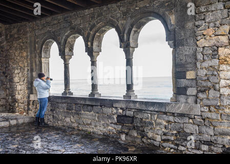 Woman female tourist taking pictures with a camera from the loggia of San Pietro, Portovenere, Cinque Terre, Liguria, Italy - Stock Image