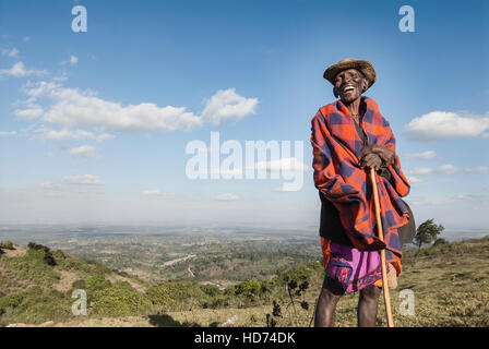 A traditional Maasai elder smiles on top of a hill with a scenic view of Kenya in background. Kenya, Africa. - Stock Image