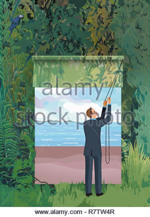 Businessman opening blind revealing window to tranquil beach in dense forest - Stock Image