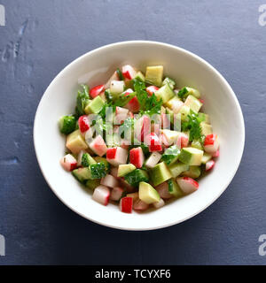 Close up of healthy vegetable salad from avocado, radish, cucumber, greens in bowl over blue stone background. Organic natural or vegetarian vegan foo - Stock Image