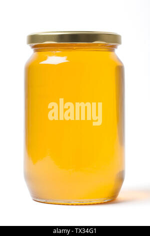 Fresh clear herbal honey in a closed clean transparent jar on white background. - Stock Image