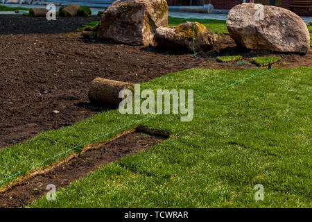 Green grass in rolls for lawn and designer landscape. The stacking of roll green lawn grass - Stock Image